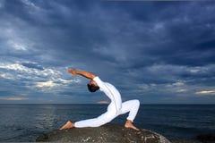 执行在石头的亚裔年轻人纵向瑜伽 免版税库存照片