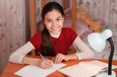 执行在笔记本的女孩家庭作业 免版税库存图片