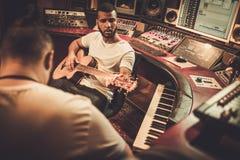 执行在精品店录音室的两个专业吉他弹奏者 免版税库存图片