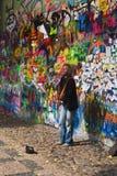 执行在约翰・列侬街道画墙壁前面的街道卖艺人 库存照片