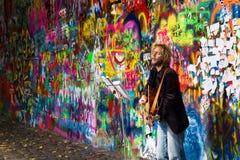 执行在约翰・列侬街道画墙壁前面的街道卖艺人 免版税库存图片