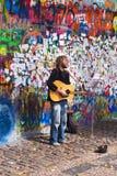 执行在约翰・列侬街道画墙壁前面的街道卖艺人 免版税图库摄影
