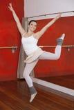 执行在舞蹈演播室的愉快的芭蕾舞女演员 免版税图库摄影