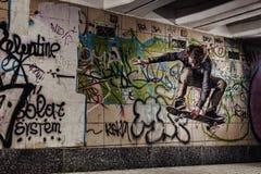 执行在街道画墙壁背景的溜冰板者劫掠 免版税库存照片