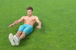 执行在运动场的年轻人仰卧起坐 免版税库存图片