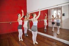 执行在镜子前面的芭蕾舞女演员 免版税库存照片
