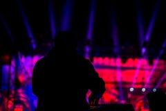 执行在阶段前面的DJ的剪影 库存照片