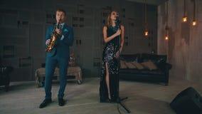 执行在阶段的发光的礼服的可爱的歌唱者与萨克斯管吹奏者爵士乐 股票录像