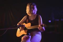执行在音乐音乐会的女性吉他弹奏者 库存图片