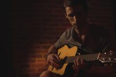执行在音乐音乐会的男性吉他弹奏者 库存照片