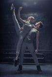 执行在黑墙壁前面的纯熟舞蹈家 免版税库存图片