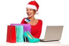 执行在兴奋礼品下的背景采购的圣诞节计算机她的互联网查出膝上型计算机位于的在线购物事空白赢取的妇女年轻人 免版税库存照片