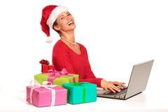执行在兴奋礼品下的背景采购的圣诞节计算机她的互联网查出膝上型计算机位于的在线购物事空白赢取的妇女年轻人 库存照片