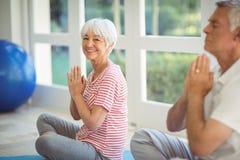执行在锻炼席子的资深夫妇瑜伽 库存照片