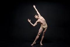 执行在黑色的熟练的年轻舞蹈家上色了演播室 免版税库存照片