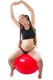 执行在fitball的一个怀孕的少妇执行 免版税库存照片