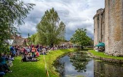 执行在Nunney城堡和护城河前面的摇摆带在Nunney,萨默塞特,英国 库存照片