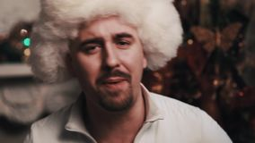 执行坐的裘皮帽的未剃须的歌手在屋子里与圣诞节装饰 股票视频