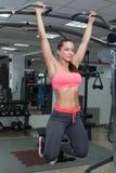 执行垂悬的腿的健身妇女提高锻炼 免版税库存图片