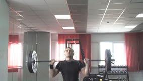 执行天花板蹲坐和推挤的运动健身男性在健身房 股票视频