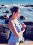 执行女子瑜伽的海滩 库存照片