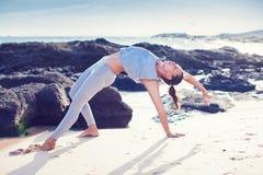 执行女子瑜伽的海滩 免版税库存照片