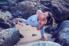 执行女子瑜伽的海滩 免版税库存图片