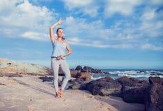 执行女子瑜伽的海滩 库存图片
