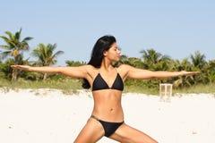 执行女子瑜伽的海滩 图库摄影