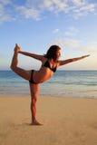 执行女子瑜伽年轻人的海滩 免版税库存照片