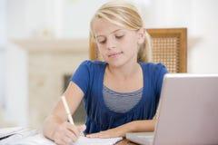 执行女孩使用年轻人的家庭作业膝上型计算机 库存照片