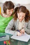 执行女孩她的家庭作业妈妈 免版税库存照片
