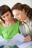 执行女孩她的家庭作业妈妈 免版税图库摄影
