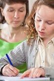 执行女孩她的家庭作业妈妈 免版税库存图片