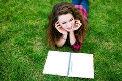 执行女孩她的家庭作业户外 库存照片