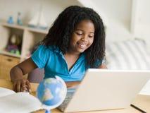 执行女孩她的家庭作业膝上型计算机年轻人 库存图片