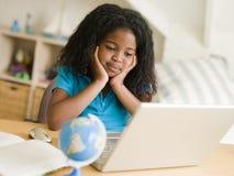 执行女孩她的家庭作业膝上型计算机年轻人 免版税图库摄影