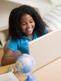 执行女孩她的家庭作业膝上型计算机年轻人 免版税库存图片