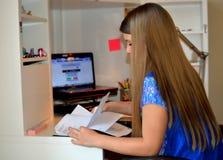 执行女孩她的家庭作业年轻人 库存图片