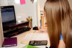 执行女孩她的家庭作业年轻人 图库摄影