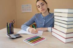 执行女孩她的家庭作业 在书桌,教育概念上的教科书 在家做教训的女孩 图库摄影