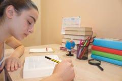 执行女孩她的家庭作业 在书桌,教育概念上的教科书 在家做教训的女孩 免版税图库摄影