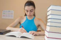 执行女孩她的家庭作业 在书桌,教育概念上的教科书 在家做教训的女孩 免版税库存照片