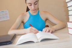 执行女孩她的家庭作业 在书桌,教育概念上的教科书 在家做教训的女孩 库存图片
