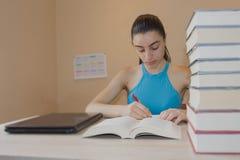 执行女孩她的家庭作业 在书桌,教育概念上的教科书 在家做教训的女孩 库存照片