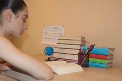 执行女孩她的家庭作业 登记概念教育查出的老 在家做教训的女孩 库存照片
