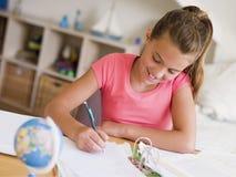 执行女孩她的家庭作业年轻人 免版税库存照片