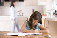 执行女孩家庭作业厨房妇女年轻人 库存照片