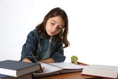 执行女孩家庭作业年轻人的子项 免版税图库摄影