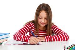 执行女孩家庭作业查出的白色的背景 免版税库存照片